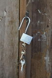 Key chain with three house or door keys on a dark wood table top. Royalty Free Stock Photos