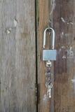 Key chain with three house or door keys on a dark wood table top. Key chain with three house or door keys on a dark wood table top Royalty Free Stock Photos
