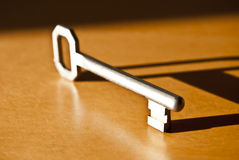 Key with clear shadow. Classic key with clear shadow on wooden surface Royalty Free Stock Image