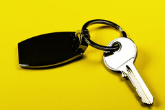 Key close-up. Clear key on keyring - yellow background isolated Stock Photos