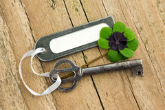 Key and clover. Key, Lucky clover and label on  board Stock Photo