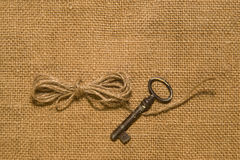 Key and a coil of rope on the old cloth Stock Photography