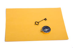 Key and compass on a sheet of paper. Key and compass on a sheet of colored plain paper with a white background Royalty Free Stock Photos
