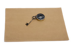 Key and compass on a sheet of paper. Key and compass on a sheet of colored plain paper with a white background Royalty Free Stock Photo