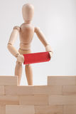 Key component. Wooden man figure holding red brick (key component) and finished the wall (structure Stock Images