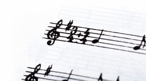 Key, double time signature symbol and violin clef. Musical notation macro, closeup. Single line sheet music detail example