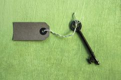 Key and an empty label on a green grunge effect background royalty free stock photos