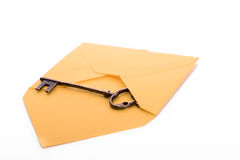 Key and envelope. Key coming out of envelope on a white background Stock Image