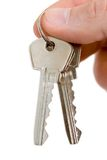 Key in fingers. On white (contains clipping path Royalty Free Stock Photo