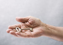 Key in hand. Senior hand holding an old key Royalty Free Stock Images