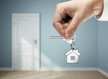 Key in hand. House key in hand against  background of room Royalty Free Stock Photography