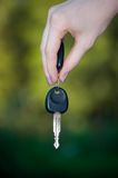 Key in a hand. On green background Royalty Free Stock Images