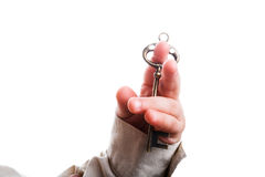 Key in hand. Baby's hand holding a  retro styled metal key  on a white background Royalty Free Stock Photo