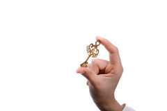 Key in hand. Hand holding a  retro styled metal key  on a white background Royalty Free Stock Image