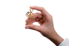 Key in hand. Hand holding a  retro styled metal key  on a white background Stock Photo