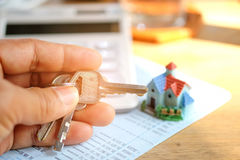Key in hand with house model and  calculator on book bank. Stock Photos