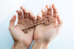 Key in hand unlock. Studio photography key in hand red shining design Stock Photos