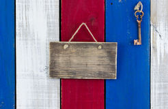 Key hanging by blank sign on colorful wood door. Blank rustic sign and bronze skeleton key hanging on red, white and blue wooden background Royalty Free Stock Images