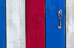 Key hanging on colorful wood old weathered door. Bronze skeleton key hanging from rope on red, white and blue rustic wooden background Royalty Free Stock Photography