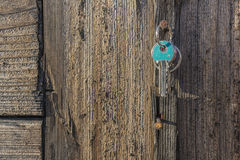 Key hanging on old rustic nail. Wooden vintage wall and aqua key Royalty Free Stock Image
