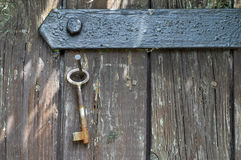 Key hanging at an old wooden door Stock Photos