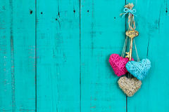 Key and hearts hanging on wood door Royalty Free Stock Photography