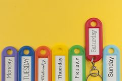 Key holders with day names on them. Yellow background Royalty Free Stock Images