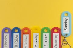 Key holders with day names on them. Yellow background Royalty Free Stock Photos