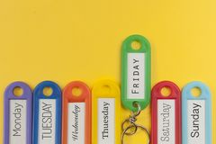 Key holders with day names on them. Yellow background Stock Photos