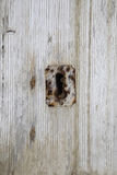 Key hole over aged gray old wood, rusty metal.  Royalty Free Stock Photography
