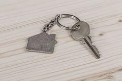 Key with home shaped keyring. A key with home shaped keyring on wooden table Royalty Free Stock Photography
