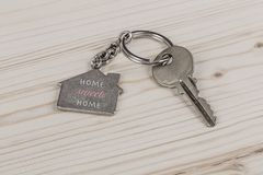 Key with home shaped keyring. A key with home shaped keyring on wooden table Royalty Free Stock Photo