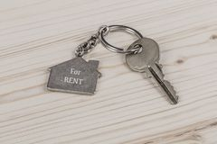 Key with home shaped keyring. A key with home shaped keyring on wooden table Stock Photography