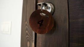 Key in hotel room door lock. Key fob with number four. Key ring from hotel room. Key with number four in castle hotel door stock video footage