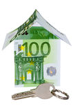 Money house with key. Silver key and a house build from 100 euro banknotes Royalty Free Stock Photo