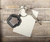 Key with house icon. On wooden background Royalty Free Stock Image
