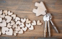 Key with house icon on wooden background Royalty Free Stock Photos