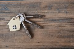 Key with house icon on wooden background Royalty Free Stock Photo