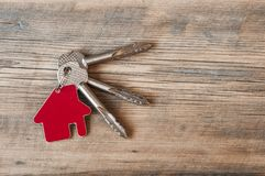Key with house icon on wooden background Stock Image
