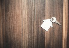 Key and house on the wood background. Business concept Royalty Free Stock Photos