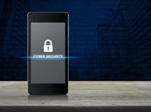 Key icon and cyber security text on modern smart phone screen on. Wooden table in front of city tower with computer binary code background, Cyber security stock images