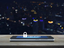 Key icon and cyber security text on modern smart phone screen on. Wooden table over city tower background, Cyber security concept stock photos