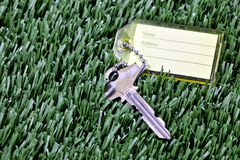 Key with ID tag laying in mown grass Royalty Free Stock Photo
