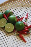 Red chili peppers and limes. royalty free stock image