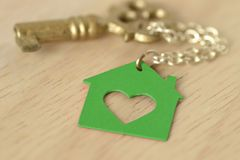 Key with a key chain in shape of a green house - Love for home a. Key with a keychain in shape of a green house - Love for home and ecology concept Royalty Free Stock Photo