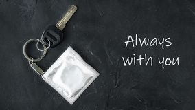 Key with keychain with grey foil mock up condom as fob on black empty chalkboard background with text Always with you, creative royalty free stock photo