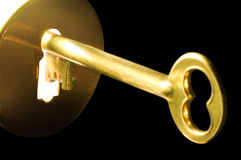 Key in the keyhole. A golden key in a keyhole illuminated by a mysterious radiant light from the other side isolated on black background Royalty Free Stock Photos