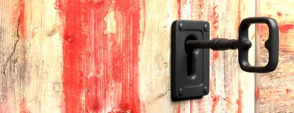 Key in a keyhole. Red wooden background. 3d illustration. Key in a keyhole on red wooden background, copy space. 3d illustration Stock Images