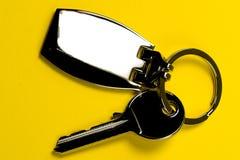 Key on keyring. Clear key on keyring , yellow background isolated Stock Photo