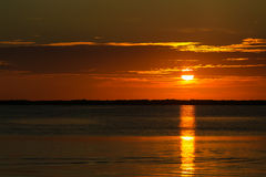 Key Largo Sunset. Tangerine sunset in Key Largo shortly before the sun is sinking into the calm sea Stock Image